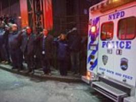 Saluting the fallen: NYPD staff pay their respects as bodies of 'executed' police officers are driven past in ambulances after gunman shoots dead two cops in their patrol car 'to get revenge for deaths of Eric Garner and Michael Brown'